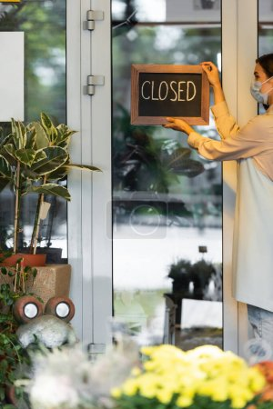 florist in medical mask putting board with closed lettering on entrance door near flowers on blurred foreground