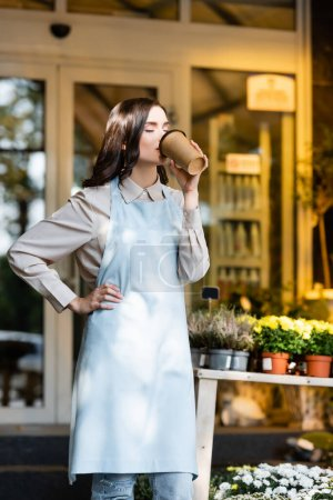 joyful florist holding hand on hip and drinking coffee with closed eyes near flower shop