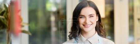 cheerful florist looking at camera near flower shop on blurred background, banner