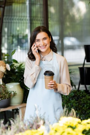 Photo for Cheerful florist talking on smartphone and holding coffee to go near blurred flowers on foreground - Royalty Free Image