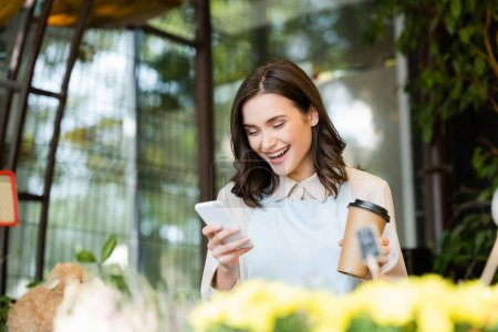 happy florist chatting on smartphone and holding paper cup near flowers on blurred foreground