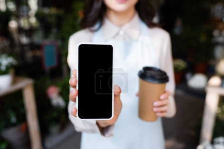 cropped view of florist holding smartphone with blank screen and coffee to go during brake on blurred background