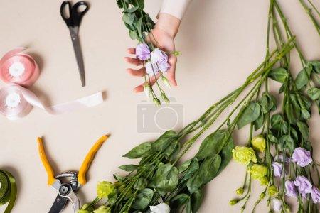 Photo pour Vue de dessus du fleuriste tenant des fleurs d'eustomes près des ciseaux, des sécateurs et du ruban décoratif tout en faisant le bouquet - image libre de droit