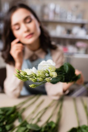 young florist holding eustoma flowers on blurred background