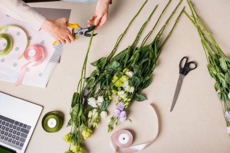 top view of florist cutting steam with secateurs while making bouquet with eustoma flowers near laptop