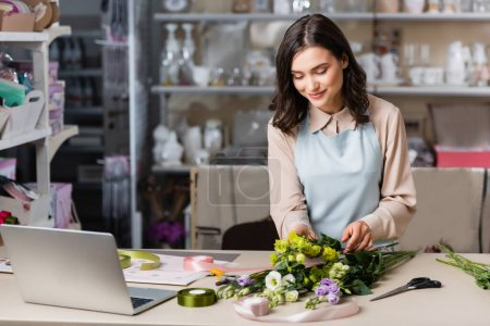 young florist making bouquet with eustoma flowers near laptop and racks on blurred background