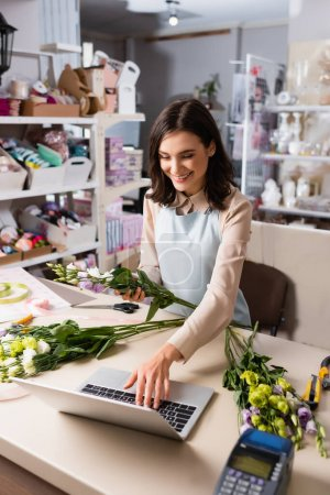 Photo for Cheerful florist using laptop while holding eustoma flowers near racks on blurred background - Royalty Free Image