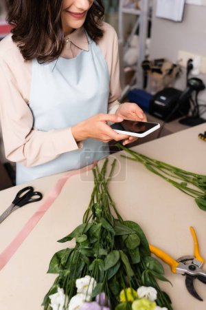 Cropped view of florist texting on smartphone, while standing near desk with eustoma flowers on blurred background