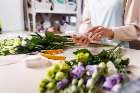 Photo pour Vue recadrée du fleuriste à l'aide d'un smartphone près du bureau avec des fleurs d'eustomie floues au premier plan - image libre de droit