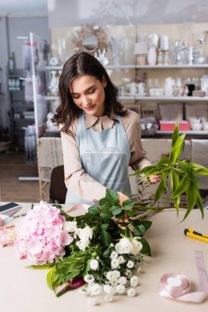 Photo pour Fleuriste souriant composer bouquet avec hortensia, chrysanthèmes et roses avec des rayonnages flous sur le fond - image libre de droit