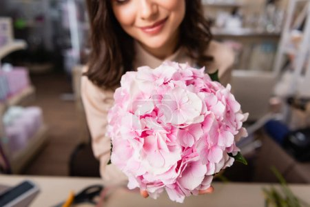 Close up view of blooming hydrangea with blurred female florist on background