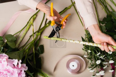 Cropped view of florist with secateurs cutting stalk of plant near flowers and decorative ribbons on desk