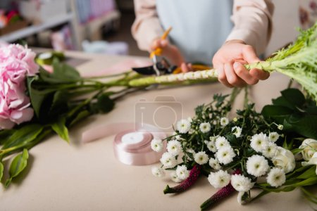 Cropped view of florist with secateurs cutting stalk of plant near flowers and decorative ribbon on desk on blurred background