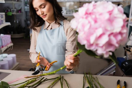 Positive female florist cutting stalk of plant near desk with blurred hydrangea on foreground