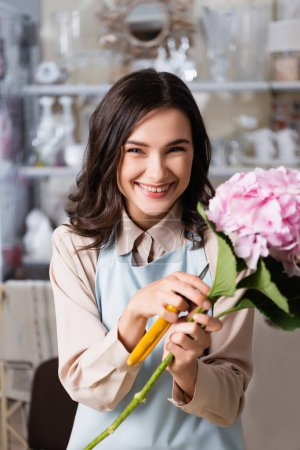 Photo pour Joyeux fleuriste féminin avec sécateurs et hortensia en fleurs regardant la caméra dans la boutique de fleurs sur fond flou - image libre de droit