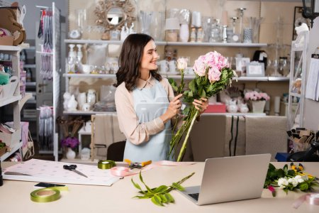 Photo for Happy florist composing bouquet with flowers, while standing near workplace with tools and laptop in flower shop - Royalty Free Image