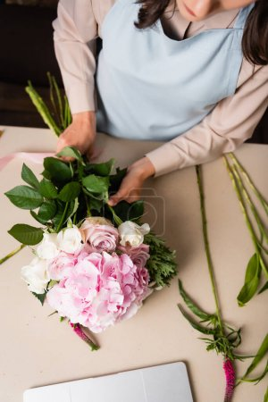 Cropped view of female florist in apron composing bouquet on desk with stalks