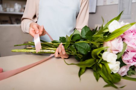 Cropped view of female florist with decorative ribbon tying stalks of fresh bouquet in flower shop on blurred background