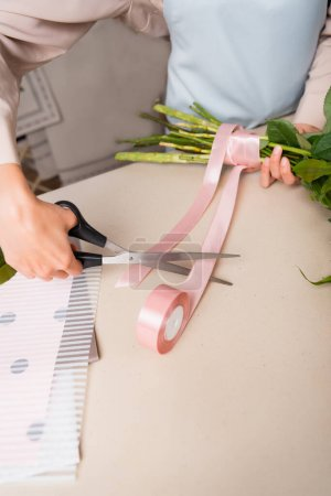 Cropped view of florist with scissors cutting decorative ribbon near tied stalks of bouquet on desk