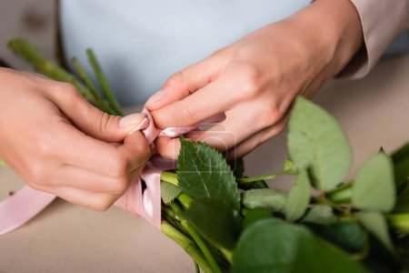 Close up view of florist hands tying stalks of bouquet with decorative ribbon on blurred background
