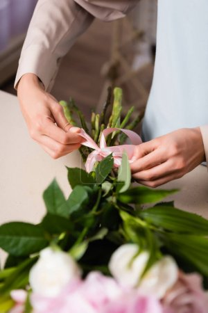 Cropped view of florist tying bow on bouquet stalks on blurred foreground