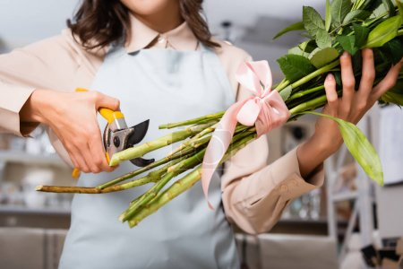 Cropped view of female florist with secateurs cutting stalks of tied bouquet on blurred background
