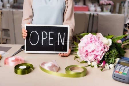 Photo for Cropped view of florist holding chalkboard with open lettering near bouquet on desk on blurred background - Royalty Free Image