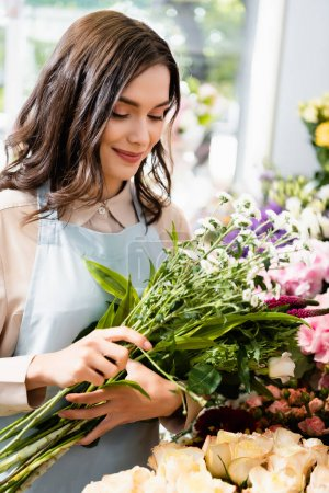 Smiling female florist holding bouquet of chrysanthemums and celosia with blurred flowers on background