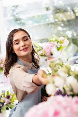 Photo pour Fleuriste souriante avec main tendue regardant des fleurs floues au premier plan - image libre de droit