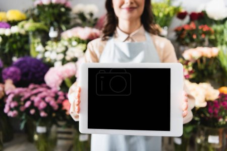 Cropped view of female florist showing digital tablet with blank screen with blurred range of flowers on background
