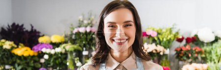 Photo for Portrait of happy florist looking at camera with blurred range of flowers on background, banner - Royalty Free Image