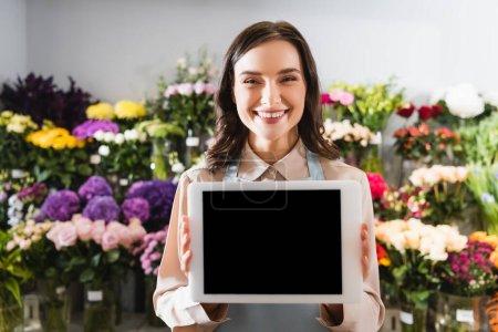 Photo pour Fleuriste féminine joyeuse montrant tablette numérique avec des étagères floues de fleurs sur fond - image libre de droit