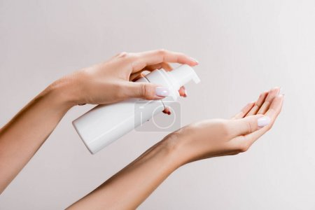 cropped view of woman applying cleansing foam isolated on grey