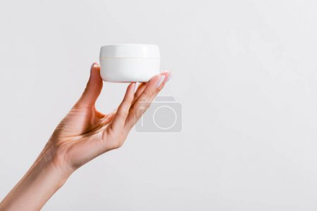 cropped view of woman holding container of hand cream isolated on grey