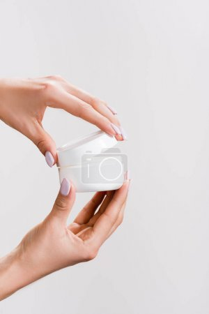 cropped view of woman opening container of hand cream isolated on grey