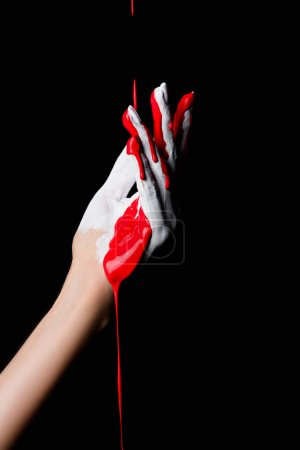 partial view of white painted hand with red dripping paint isolated on black