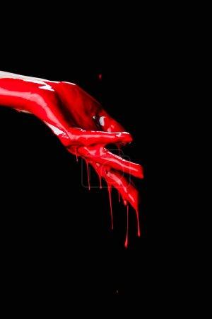Teilansicht der gemalten Hand mit roter tropfender Farbe isoliert auf Schwarz