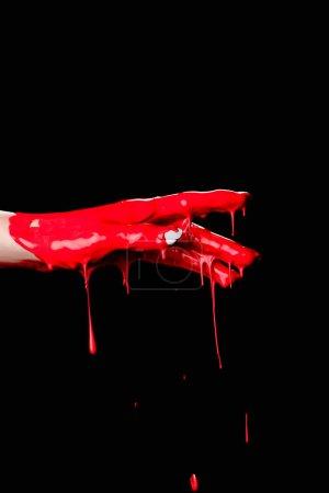 vue partielle de la main peinte avec de la peinture rouge goutte à goutte isolée sur noir