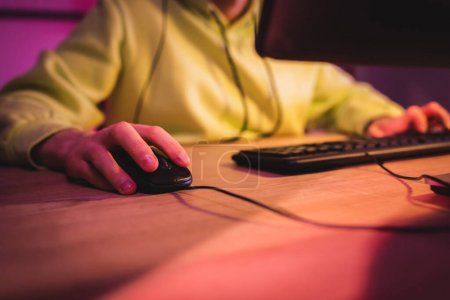 Cropped view of gamer using computer mouse near keyboard on blurred background
