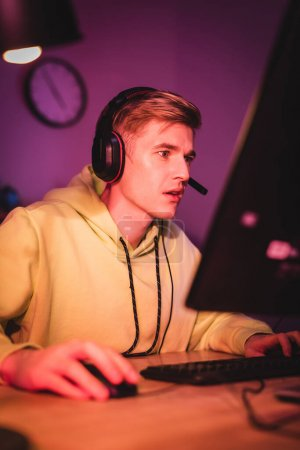 Focused man in headset playing video game on computer on blurred foreground