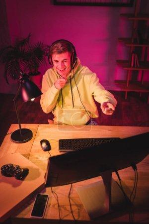 KIEW, UKRAINE - 21. AUGUST 2020: Lächelnder Gamer im Headset, der mit den Fingern auf den Computer in der Nähe von Steuerknüppel, Pizzakiste und Smartphone im verschwommenen Vordergrund zeigt