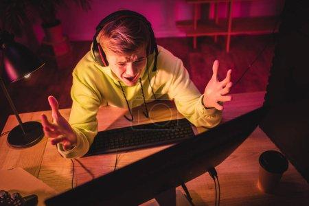 Photo pour KYIV, UKRAINE - 21 AOÛT 2020 : Vue aérienne d'un joueur inquiet dans un casque regardant un écran d'ordinateur près d'un café à emporter et un joystick au premier plan flou - image libre de droit