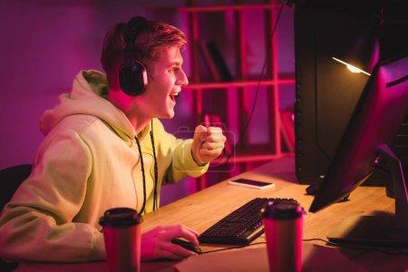 Fröhlicher Gamer zeigt Yah-Geste in der Nähe von Computer, Coffee to go und Smartphone auf verschwommenem Hintergrund