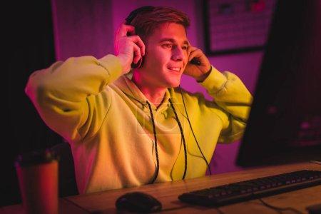 Photo pour Gamer souriant portant un casque près de l'ordinateur et du café pour aller sur le premier plan flou - image libre de droit