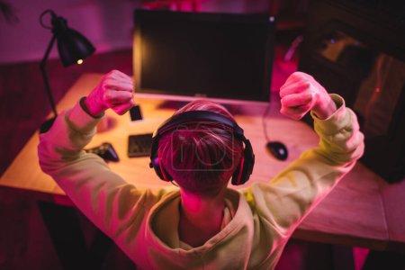Vue aérienne du joueur dans les écouteurs montrant un geste ouais près de l'ordinateur et un joystick sur fond flou