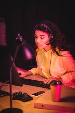 KYIV, UKRAINE - 21 AOÛT 2020 : Joueur afro-américain excité dans un casque à l'aide d'un ordinateur près d'un joystick, d'un smartphone et d'une boîte à pizza au premier plan flou