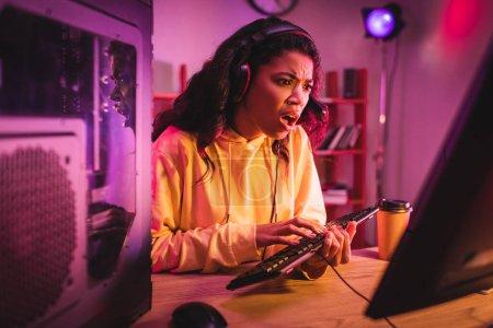 Photo pour Joueur afro-américain insatisfait dans un casque en utilisant un clavier d'ordinateur près du café pour aller - image libre de droit