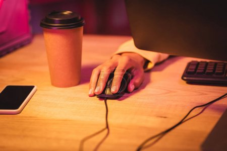 Cropped view of gamer using computer mouse near smartphone with blank screen and coffee to go