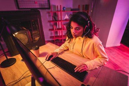 Photo pour Choqué gamer afro-américain dans casque en utilisant l'ordinateur pendant le jeu vidéo près de café pour aller - image libre de droit