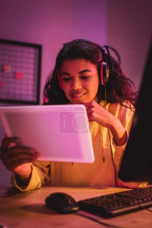 Smiling african american gamer in headset holding digital tablet on blurred foreground